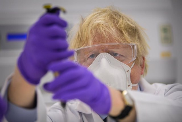 HANDOUT - 28 January 2021, United Kingdom, Edinburgh: UK Prime Minister Boris Johnson tries his hand at one of the tests as he visits the French biotechnology laboratory Valneva in Livingston where they will be producing a Covid-19 vaccine on a large scal