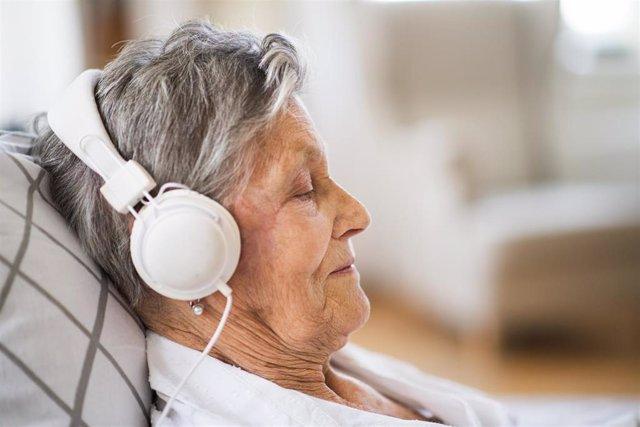Mujer mayor escuchando música.