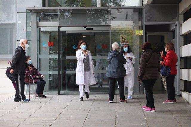 Varias trabajadoras sanitarias hablan con pacientes que esperan en la puerta del Centro de Salud Doctor Tamames