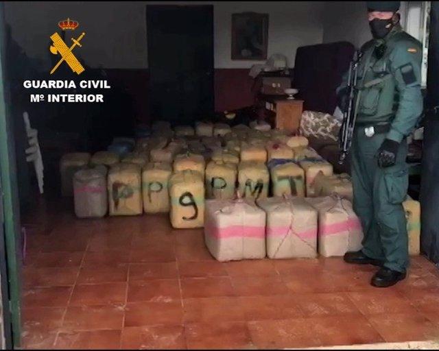 Un agente de la Guardia Civil custodia los kilogramos incautados en la operación Impasible desarrollada en Málaga y Cádiz