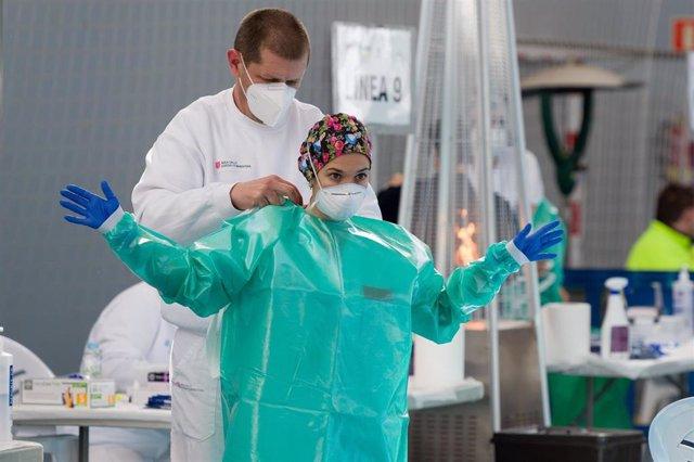 Una trabajadora sanitaria se protege para realizar tests de antígenos