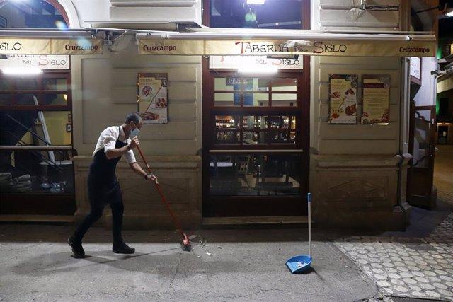 Dos camareros se afanan en recogen la terraza del bar ubicado en el centro de la capital, como  consecuencia del toque de queda impuesto por el Gobierno para poder frenar el contagio en Málaga a 27 de octubre 2020