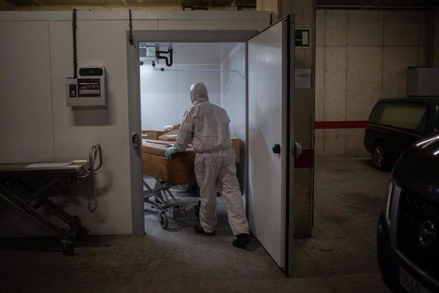 Un operario del Crematorio de Girona totalmente protegido traslada un ataúd de una víctima con COVID-19 para desinfectarlo antes de introducirlo en el horno crematorio. En Girona, Cataluña, (España), a 6 de mayo de 2020.