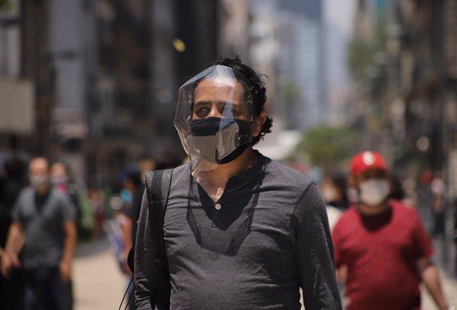 Un hombre camina por las calles de Ciudad de México con extra de protección contra el COVID-19.