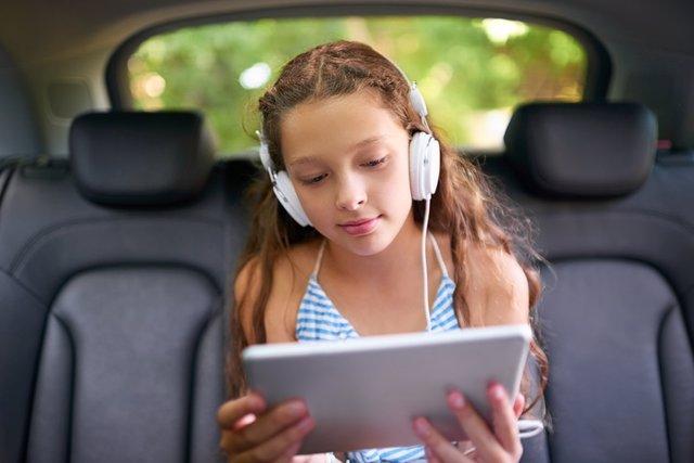 Adolescentes, tablet, coche, viaje, cascos.