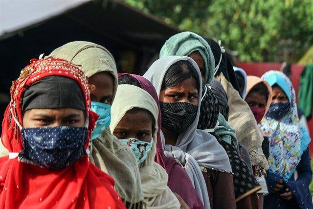 Refugiadas rohingyas con mascarilla hacen cola para un chequeo médico en Indonesia