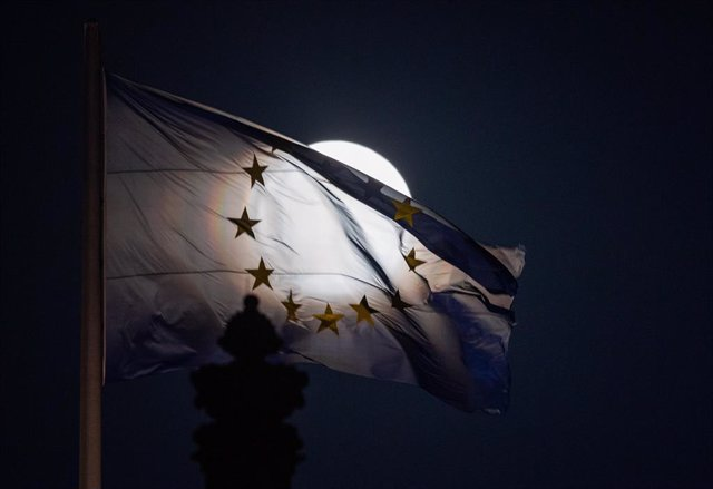 07 April 2020, Berlin: The so-called pink supermoon rises behind an EU flag on the Reichstag building. Photo: Christophe Gateau/dpa