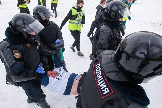 Un manifestante detenido por agentes antidisturbios en San Petersburgo, en Rusia, durante las protestas contra el encarcelamiento del activista opositor Alexei Navalni