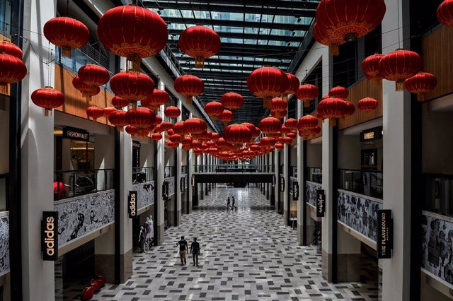 27 January 2021, Malaysia, Kuala Lumpur: People walk beneath decorative Chinese lanterns that have been hung at a shopping mall in preparation for the Chinese New Year celebrations, scheduled to take place on 12 February 2021. Photo: Amirul Azmi/BERNAMA/d