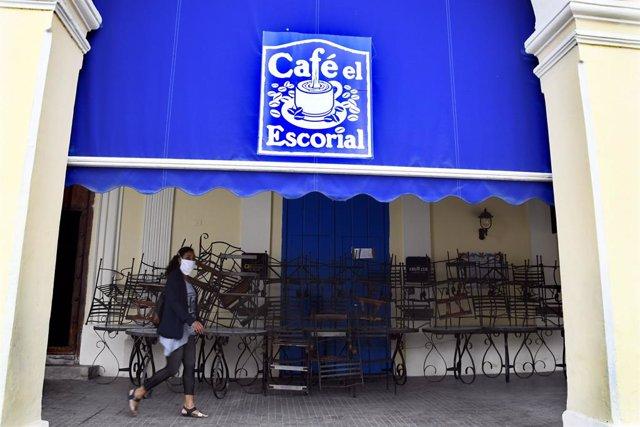 Una mujer pasea ante una cafetería en La Habana