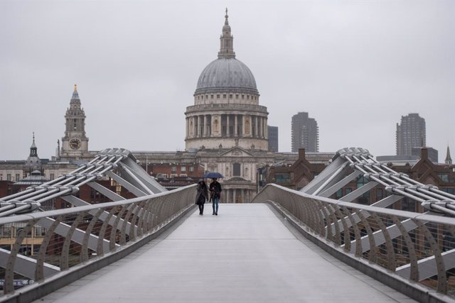 21 December 2020, England, London: Two people cross the quiet Millennium Bridge in London. UK Prime Minister Boris Johnson announced a strict lockdown and cancelled Christmas holiday gatherings across London and eastern and south-east England after scient