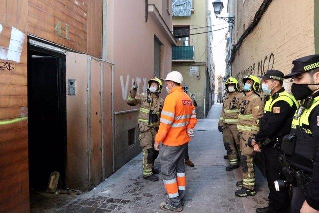 Efectivos de la Policía Local y del Cuerpo de Bomberos inspeccinan el edificio incendiado de la calle Cerezo, 41 de Zaragoza antes de tapiarlo