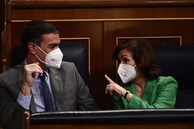 El presidente del Gobierno, Pedro Sánchez, conversa con la vicepresidenta primera del Gobierno, Carmen Calvo, durante la primera sesión de control al Gobierno de 2021 celebrada en el Congreso de los Diputados, en Madrid, (España), a 3 de febrero de 2021