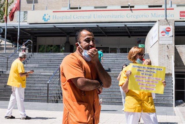Trabajadores sanitarios silban durante la concentración convocada donde decenas de celadores se han congregado a las puertas del Hospital General Universitario Gregorio Marañón, tras ser excluidos de la catalogación de personal de riesgo. En Madrid, (Espa