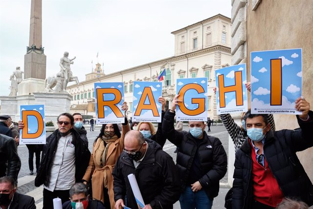 03 February 2021, Italy, Rome: Supporters of former President of the European Central Bank Mario Draghi hold placards upon his arrival at the Quirinal Palace for a meeting with Italian President Sergio Mattarella for consultations to form a new government