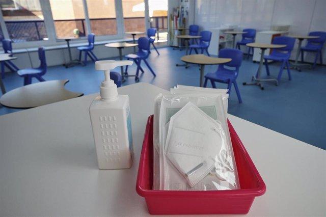 Mascarillas y gel desinfectante en la mesa del profesor de un aula