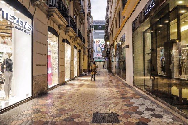 Una calle comercial de Valencia con todos sus establecimiento cerrados.