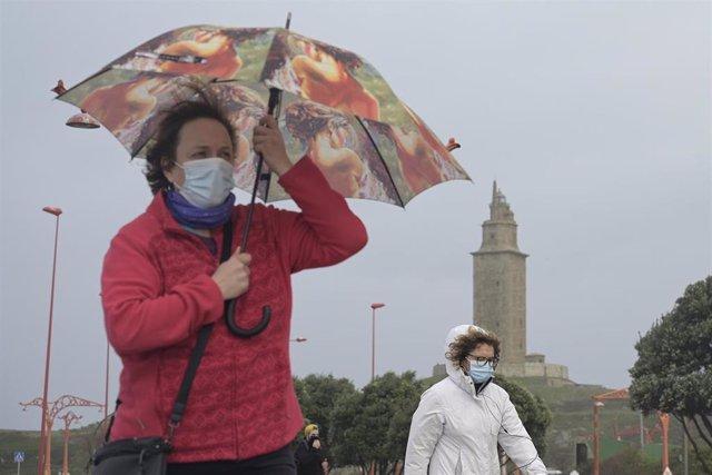 Dos mujeres caminan en un día de lluvia por el Paseo Marítimo de A Coruña (Galicia)