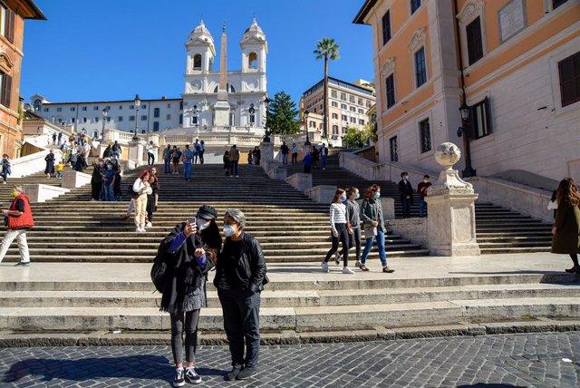 Turistas con mascarilla en la Plaza de España de Roma