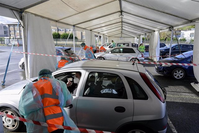 Una hombre muestra el DNI a un sanitario para recoger su test de saliva desde el coche en la Avenida de Arsenio Iglesias en Arteixo, A Coruña, Galicia (España), a 24 de enero de 2021. El Servizo Galego de Saúde (Sergas) ha citado mediante un mensaje a los