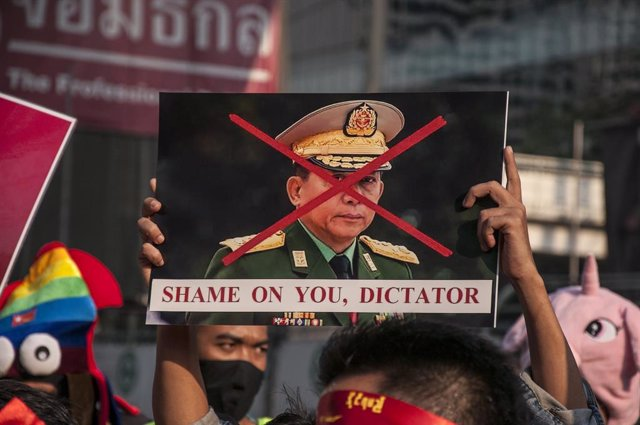 01 February 2021, Thailand, Bangkok: Ademonstrator holds a crossed-out poster of Myanmar's army chief Min Aung Hlaing during a protest outside Myanmar's embassy in Bangkok, after Myanmar's military seized power from the de facto leader Aung San Suu Kyi a