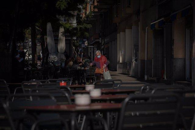 Una mujer en una terraza durante el primer día del inicio del primer tramo de la desescalada de la segunda ola por el coronavirus en Barcelona, Catalunya (España), a 23 de noviembre de 2020. Desde hoy, bares y restaurantes podrán abrir de 6.00 a 21.30 par