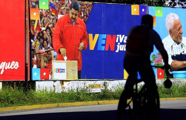 Un cartel con Nicolás Maduro depositando el voto