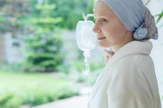 Mujer con gotero mirando por la ventana.