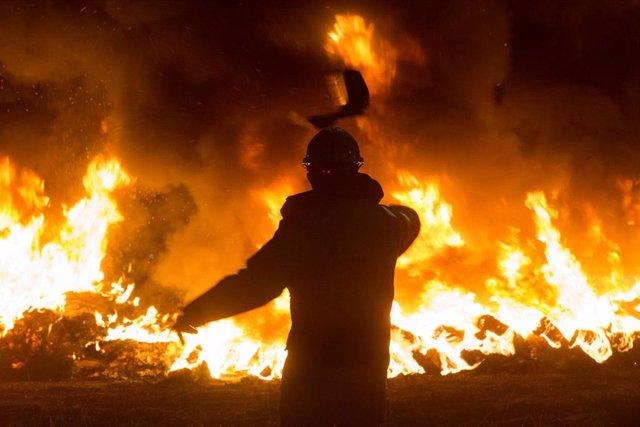 Un trabajador tira un elemento a una barricada durante un velatorio nocturno simbólico convocado por la fábrica de Alcoa.