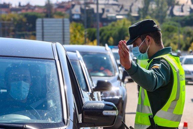 Un agente de la Guardia Civil da el alto a un vehículo en un control dentro de las medidas de prevención de la Covid-19