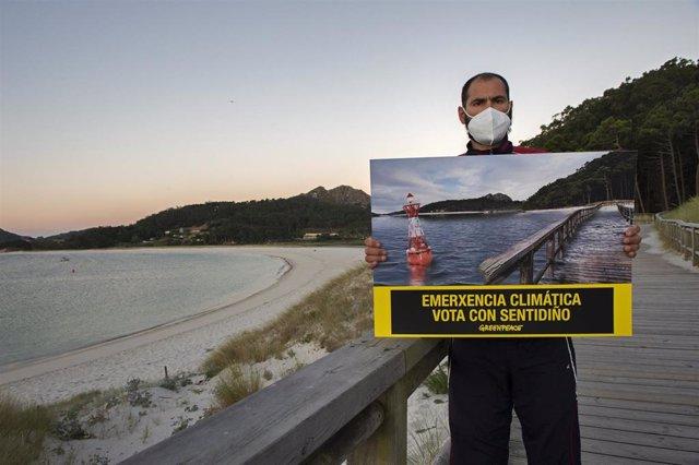 Un voluntario de Greenpeace porta una fotografía modificada de la Praia de Rodas, en las Illas Cíes, para simular los efectos de la subida del nivel del mar