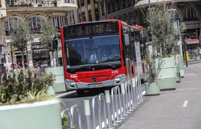 Un autobús de la línea C1 pasa al lado de los maceteros colocados en la Plaza del Ayuntamiento de Valencia
