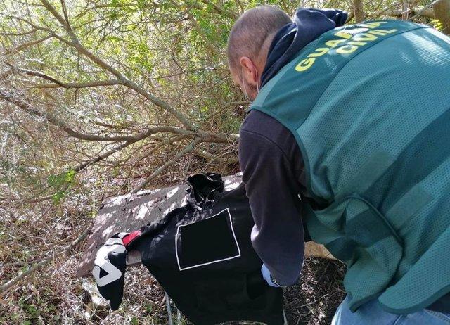 Un guardia civil examina una pieza de ropa que pertenecería al presunto agresor sexual de Felanitx.