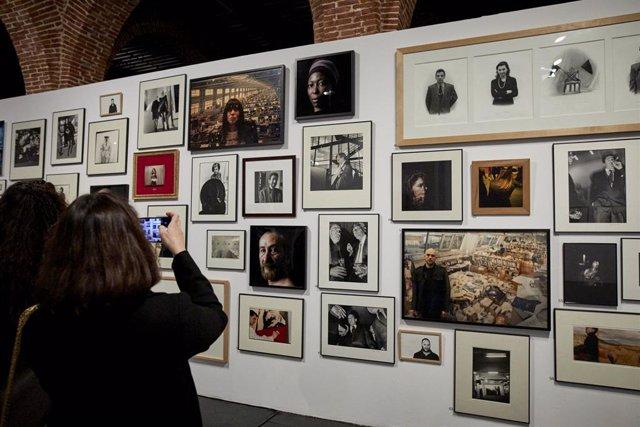 Varias personas visitan la exposición 'Arco. Recorridos Fotográficos' en Condeduque, en Madrid (España).