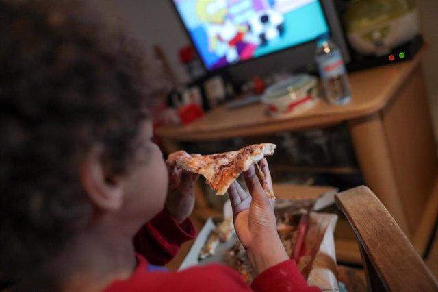 Un niño come un trozo de pizza del menú infantil de Telepizza mientras ve la televisión en su casa, tras recoger el menú en un establecimiento de Telepizza.