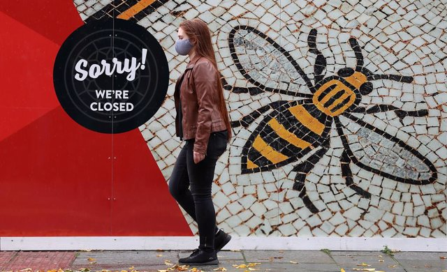 20 October 2020, England, Manchester: A person wearing a face mask walks past a poster of the Manchester Bee in Albert Square as the Government is preparing to impose stringent new coronavirus controls on 2.8 million people after talks with the local lead
