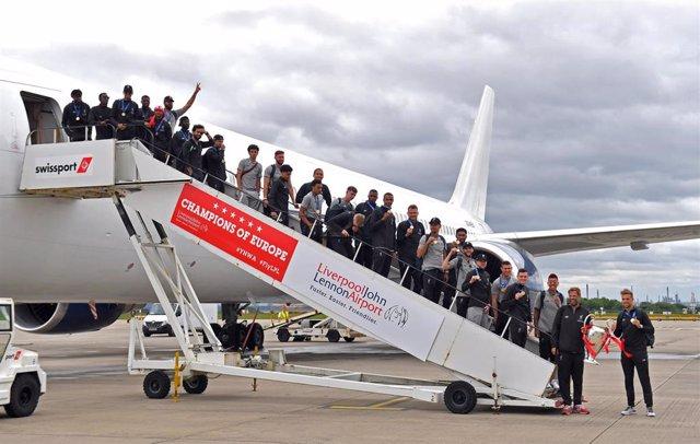 La plantilla del Liverpool posa con la Champions al bajar del avión de regreso a casa en 2019