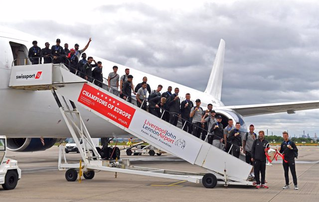 02 June 2019, England, Liverpool: Members of the Liverpool FC team pose for a picture with the trophy as they descend from their plane upon arrival at the John Lennon Airport a day after they won the UEFA Champions League final soccer match against Totten