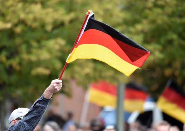 08 September 2019, North Rhine-Westphalia, Moenchengladbach: A demonstrator waves a German flag at the rally of right-wing groups. A large contingent of the police accompanied a rally of right-wing groups and the counter-demonstration of predominantly bou