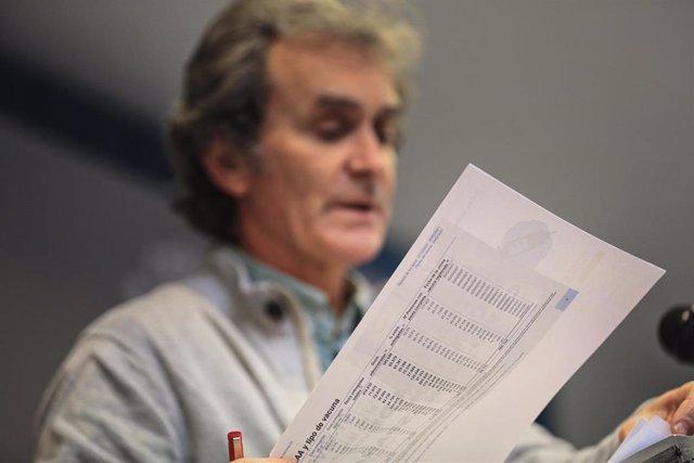 El director del Centro de Coordinación de Alertas y Emergencias Sanitarias (CCAES), Fernando Simón con documentos durante una rueda de prensa convocada ante los medios de comunicación en el Ministerio de Sanidad para informar sobre la evolución del corona