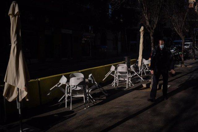 """Un hombre pasa al lado de las sillas vacías de una terraza en Barcelona, Catalunya (España), a 21 de diciembre de 2020. Debido al incremento de la curva de la pandemia en Catalunya y ante """"la posible llegada de una tercera ola que incremente el nivel de p"""