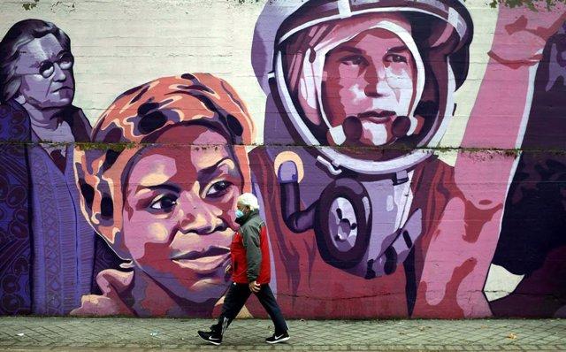 Un hombre pasa por el mural feminista en el polideportivo municipal de la Concepción en el distrito de Ciudad Lineal