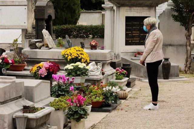 Una mujer visita una tumba ubicada en un cementerio de Niza, Francia, durante la pandemia de COVID-19.