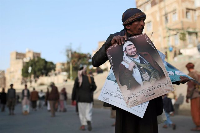25 January 2021, Yemen, Sanaa: A Yemeni vendor displays portraits of the leader of the Houthis, Abdul-Malik al-Houthi, to sell them for the demonstrators during a rally against the United States over its decision to designate the Houthi rebels movement as