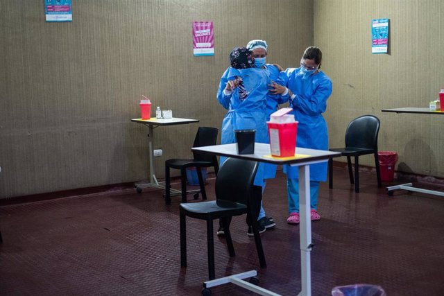 Profesionales sanitarios se abrazan en la campaña de vacunación.