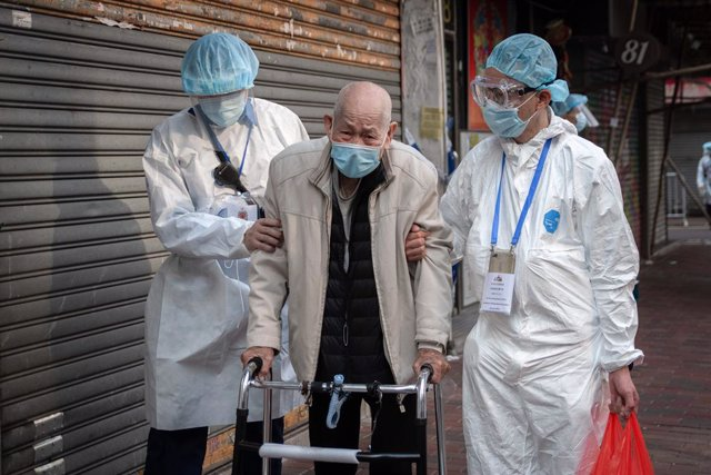 23 January 2021, China, Hong Kong: Health workers help an elderly resident returning home in an area where unprecedented lockdown has been declared by Hong Kong government in order to carry out compulsory coronavirus (COVID-19) testing in a designated zon