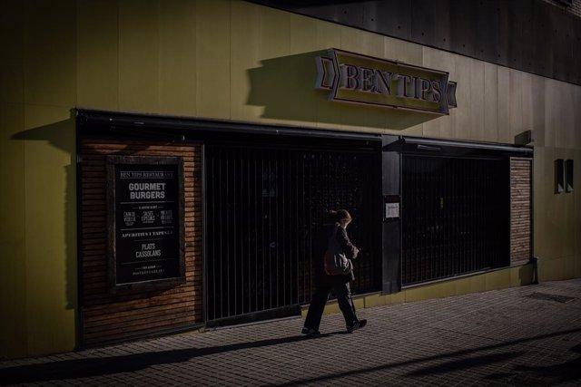 Un home passa per un bar tancat a Barcelona. (Arxiu)