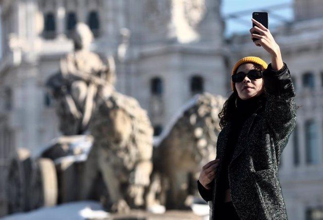 Una mujer se hace un selfie junto a la estatua de Cibeles, en Madrid (España), a 11 de enero de 2021.