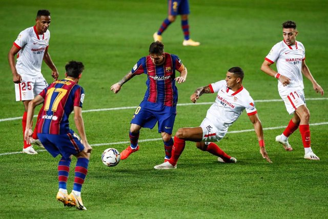 10 Lionel Messi of FC Barcelona defended by 20 Diego Carlos of Sevilla FC during La Liga match between FC Barcelona and Sevilla FC at Camp Nou Stadium on October 04, 2020 in Barcelona, Spain.