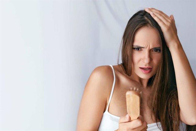 Hair Loss. Upset Woman Holding Brush With Hair. Pelo, caída de pelo, mujer ,injerto capilar